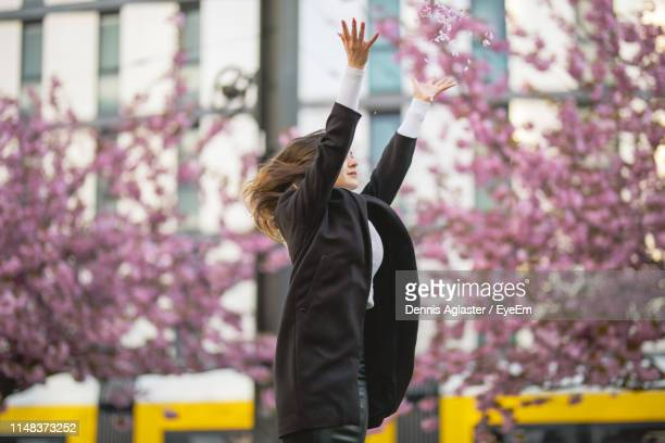 woman with arms raised throwing flowers standing against building in city - 投げる ストックフォトと画像