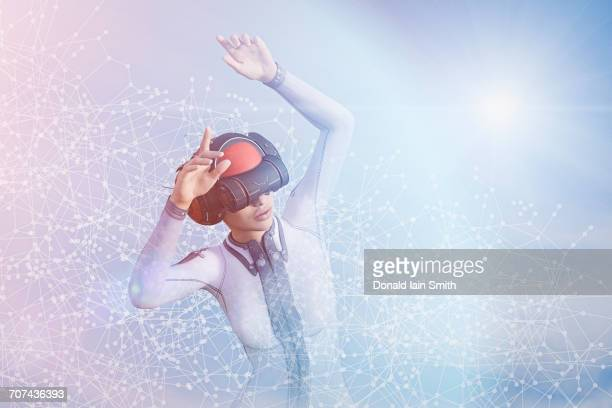 Woman with arms raised using virtual reality helmet