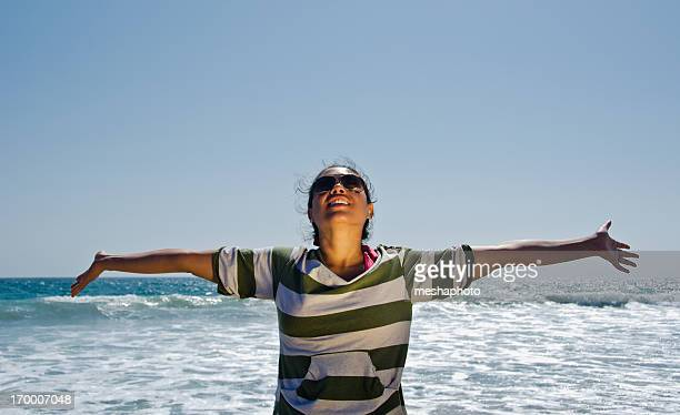 Woman with arms stretched looking at sky at the beach