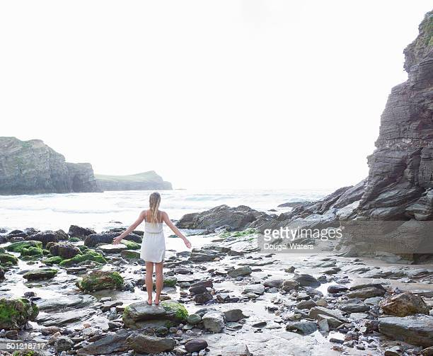 Woman with arms stretched standing on rocky coast