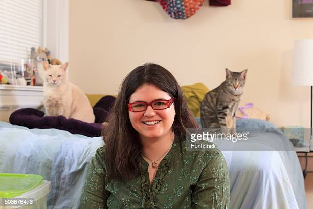woman with asperger syndrome playing with her pet cats - autism spectrum disorder stock photos and pictures