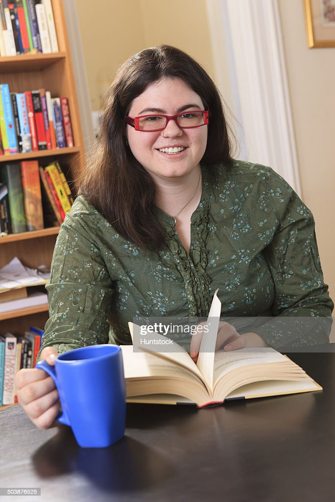 Woman with Asperger syndrome relaxing with a mug of tea and a book : Stock Photo