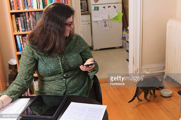 Woman with Asperger syndrome working in her home office and watching her cat