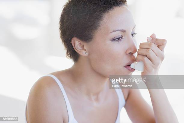 woman with asthma using inhaler - asthmatic stock photos and pictures