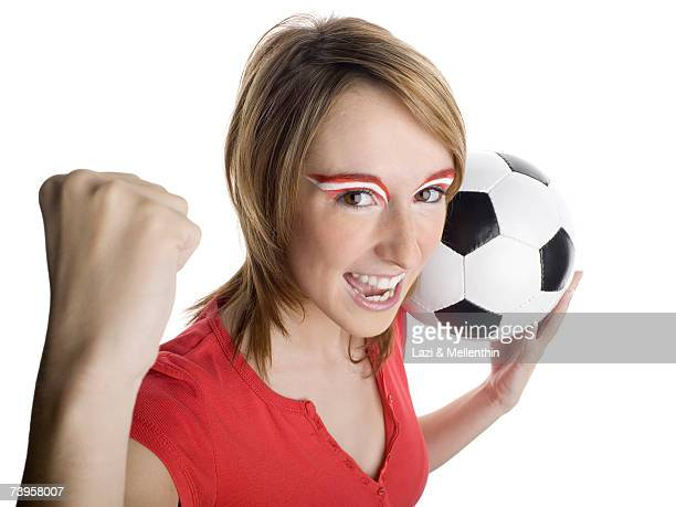 Woman with Austrian flag painted on eyebrows holding football, clinching fist, portrait, smiling