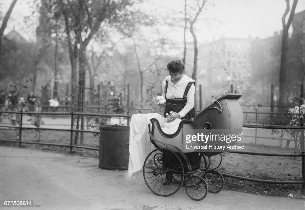 Woman with Baby Carriage Holding Milk Bottles from Depot set up by merchant Nathan Straus that Provides Pasteurized Milk to Poor Families, New York...