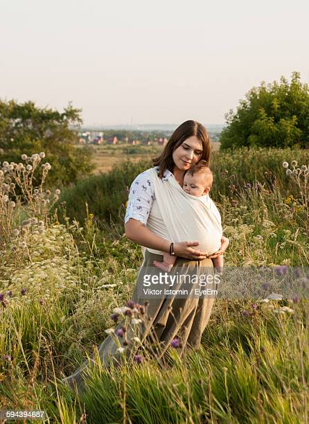 Woman With Baby Carrying In Fabric While Standing On Field Against Sky
