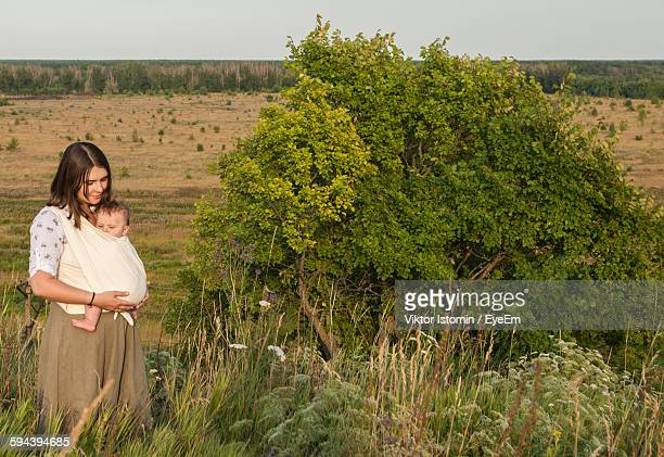 Woman With Baby Carrying In Fabric While Standing On Field