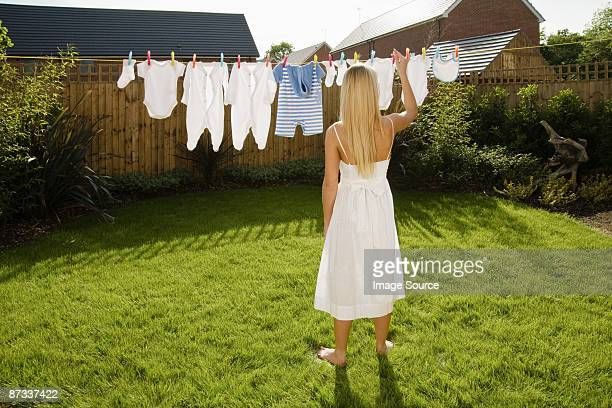 Woman with baby clothes on clothes line
