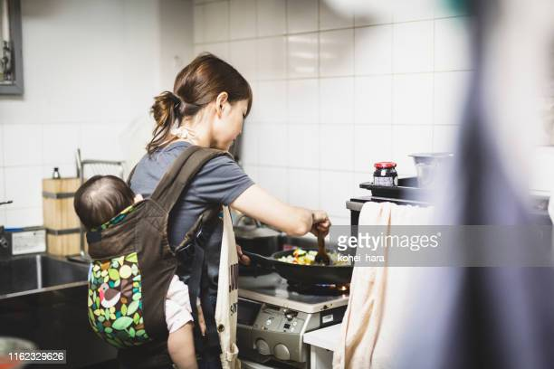 woman with baby cooking in the kitchen - single mother stock pictures, royalty-free photos & images