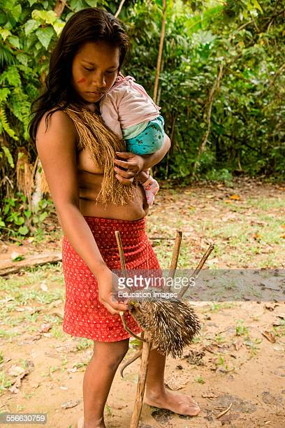 Woman with baby feeds pet porcupine in village on the Amazon River Peru