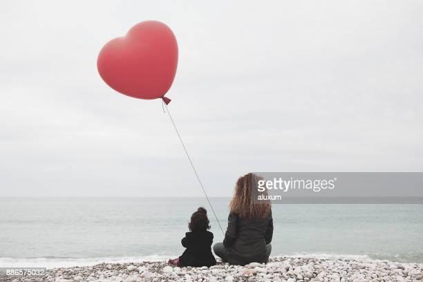 mujer con bebé niña y corazón globo mirando el mar - esperanza fotografías e imágenes de stock