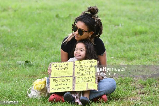 Woman with baby holds a placard with anti-vaccination and anti-coronavirus lockdown messages during a demonstration in Hyde Park in London on May 16...
