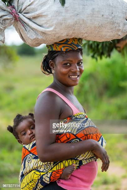 woman with baby is carrying a big load on her head, dr congo - congo stock pictures, royalty-free photos & images