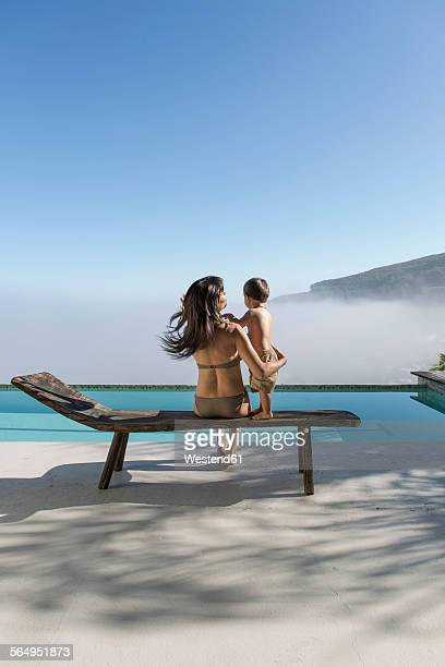 Woman with baby on a lounge next to pool