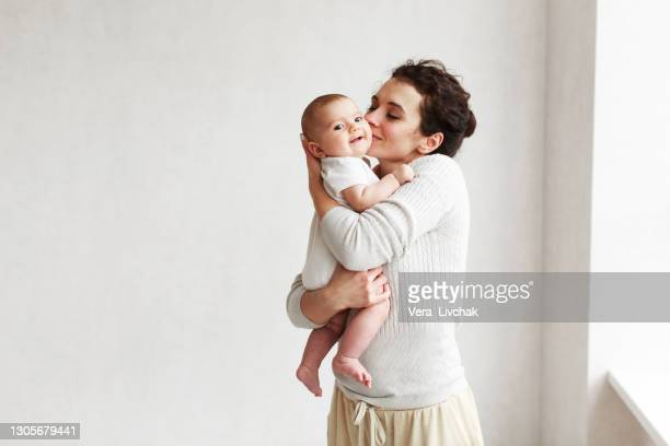 woman with baby on white background - baby stock pictures, royalty-free photos & images