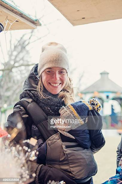 "woman with baby shopping in outdoors public market in winter. - ""martine doucet"" or martinedoucet stock pictures, royalty-free photos & images"