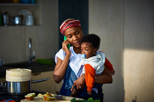 Woman with baby son in kitchen - gettyimageskorea