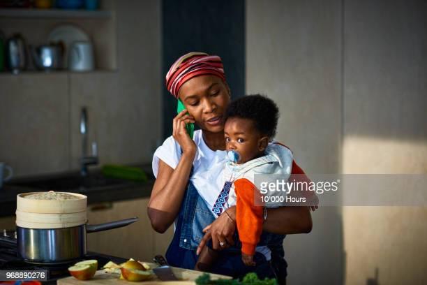 woman with baby son in kitchen - black cook fotografías e imágenes de stock