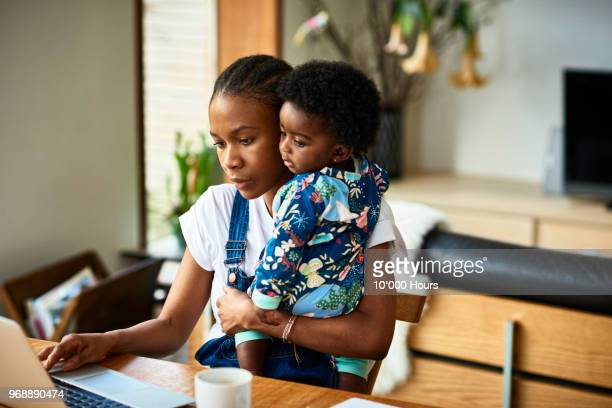 woman with baby son working - affaires finance et industrie photos et images de collection