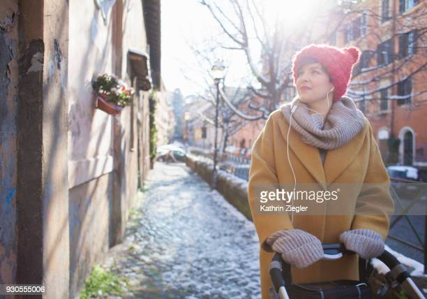 Woman with baby stroller in wintery Rome, ground covered with snow