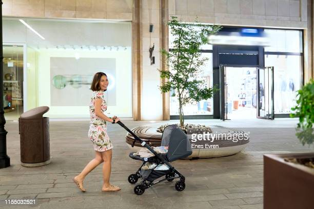 Woman with baby stroller on street