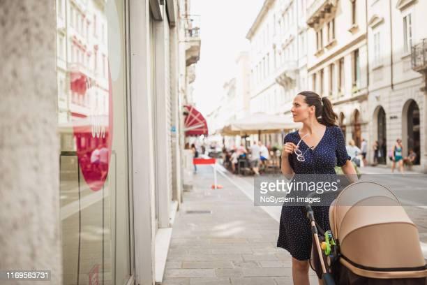 ベビーカーの窓の買い物を持つ女性 - 乳母車 ストックフォトと画像
