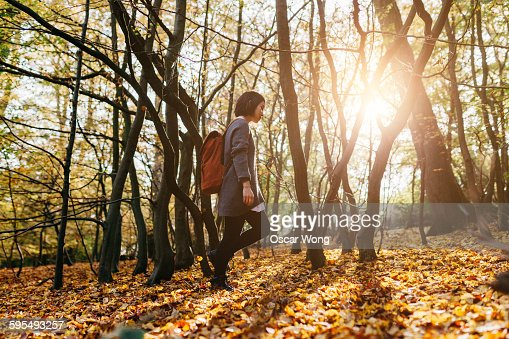 Woman with back pack walking through woodland