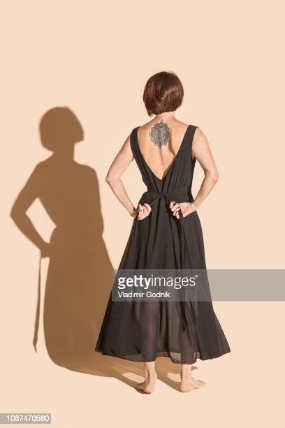 woman with back tattoo tying black dress - femme brune de dos photos et images de collection