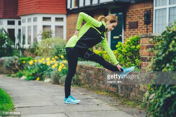 woman with backache after jogging - jogging stock pictures, royalty-free photos & images