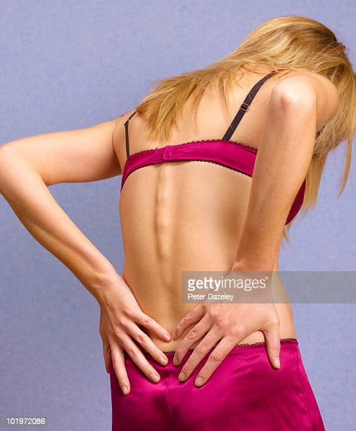 woman with backache bad back - liesbreuk stockfoto's en -beelden