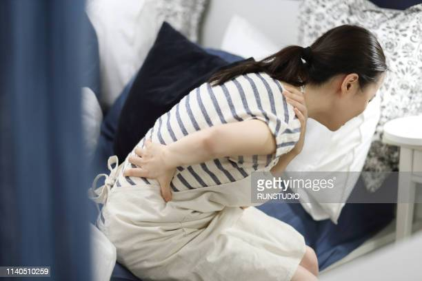 woman with backache in bedroom - 背痛 ストックフォトと画像