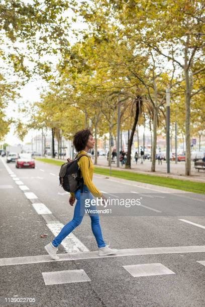 woman with backpack crossing the street - 背景に人 ストックフォトと画像