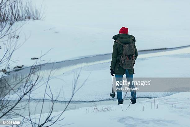 Woman with backpack holding camera while standing on field during winter