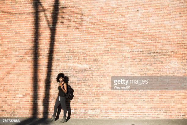 woman with backpack in front of brick wall with shadow of a power pole - ニューヨーク州 ブルックリン ストックフォトと画像