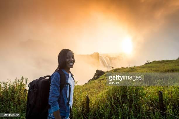 Vrouw met rugzak bij zonsopgang kijken naar Victoria Falls