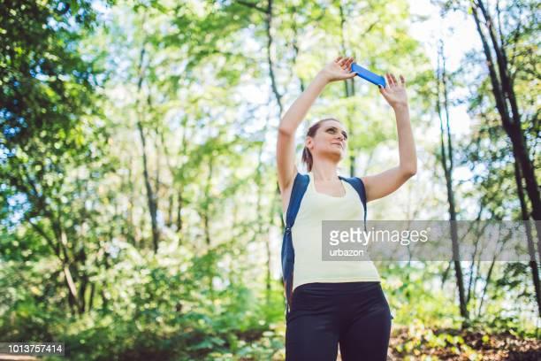 mulher com mochila fazendo foto de paisagem bela floresta. - atividades ao ar livre - fotografias e filmes do acervo