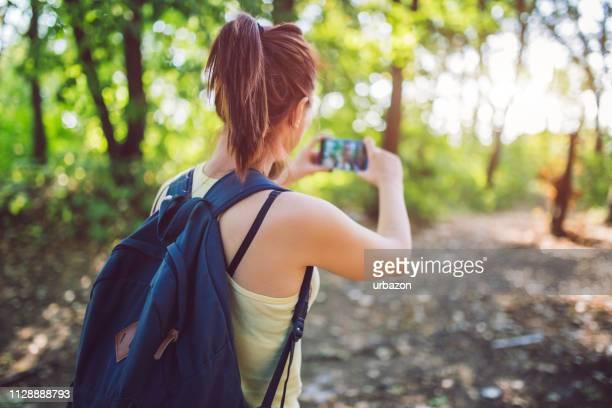 mulher com mochila fazendo selfie e andando pela floresta. - atividades ao ar livre - fotografias e filmes do acervo