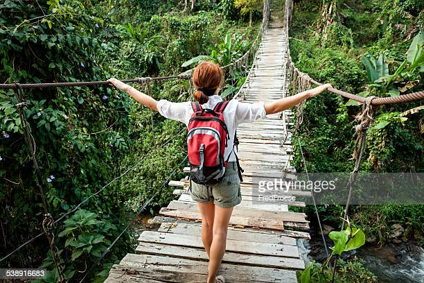 Woman with backpack on suspension bridge in rainforest jungle