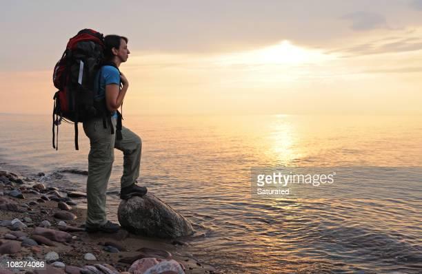 mujer con mochila con vista a la puesta de sol sobre el agua - parque estatal de porcupine mountains wilderness fotografías e imágenes de stock