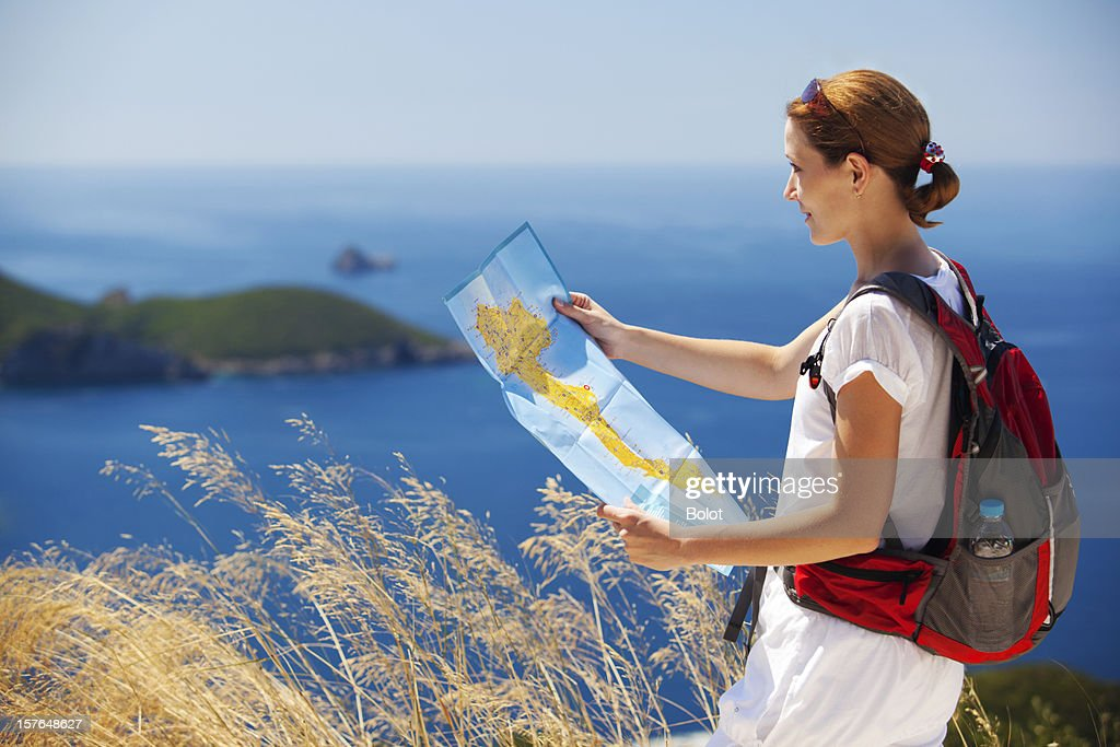 Woman with backpack reading map : Stock Photo