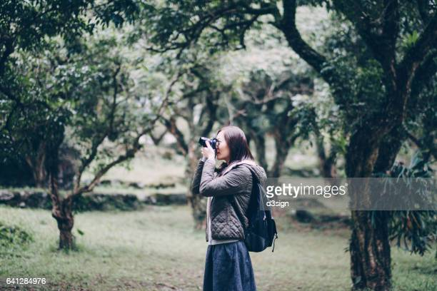 woman with backpack taking photos in woodland - leanincollection stock pictures, royalty-free photos & images