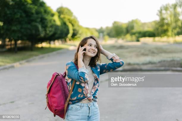 路上で携帯電話で話しているバックパックを持つ女性 - ワインレッド ストックフォトと画像