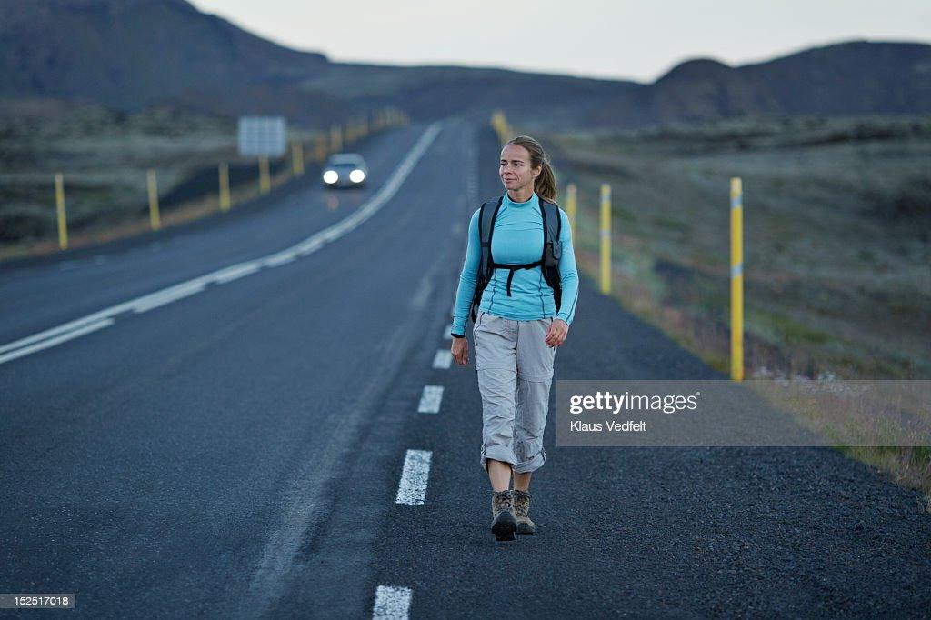 Woman with backpack walking alongside long road : Foto stock