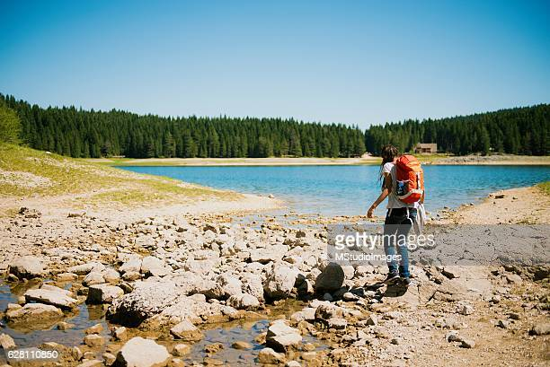 Woman with backpack walking in nature.