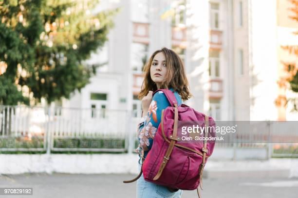 通りを歩いてバックパックを持つ女性 - ワインレッド ストックフォトと画像