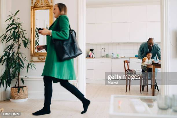 woman with bag walking in living room while man playing with daughter at table - stay at home father stock pictures, royalty-free photos & images