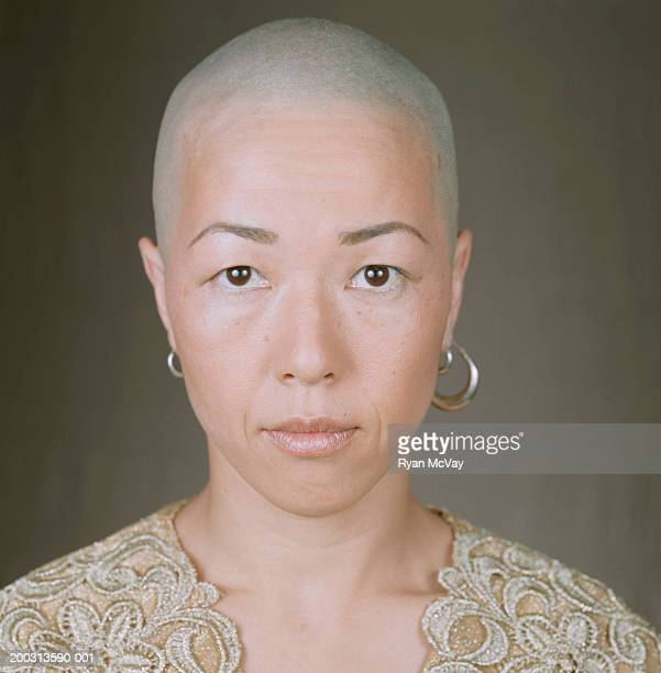 woman with bald head and earrings, posing in studio, portrait - shaved head stock pictures, royalty-free photos & images