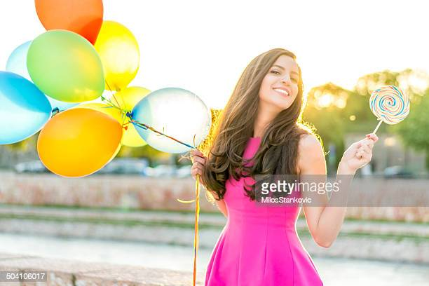 Woman with balloons and lollipop