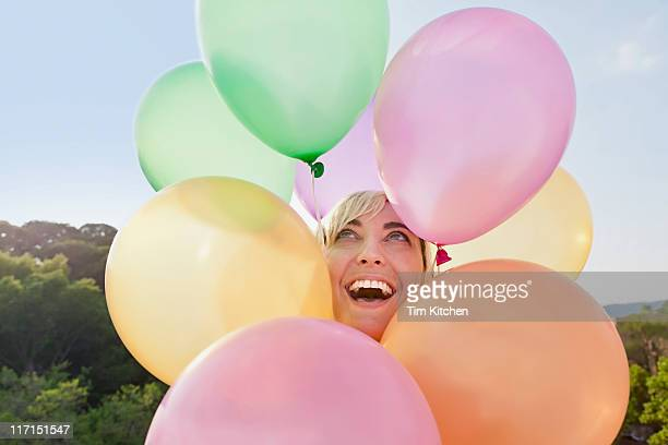 Woman with balloons circling head, smiling